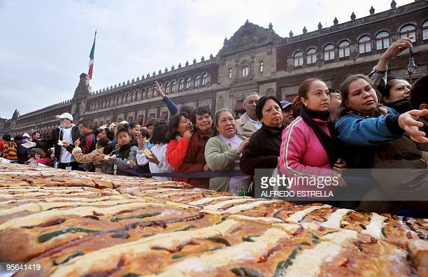 People crowd together while waiting for a piece of the traditional Rosca de Reyes a large bread roll baked for Epiphany in Mexico City on January 3...