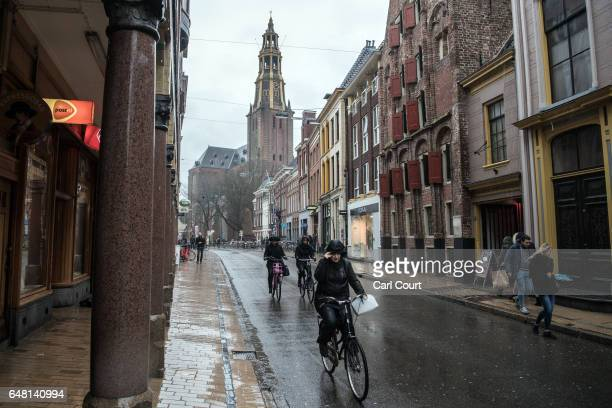 People cycle along a street on February 23 2017 in Groningen Netherlands The Dutch will vote in parliamentary elections on March 15 in a contest that...
