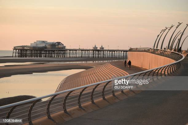 People cycle along the front toweards the north pier in the evening sunshine in Blackpool northwest England on March 26 2020 The coronavirus outbreak...