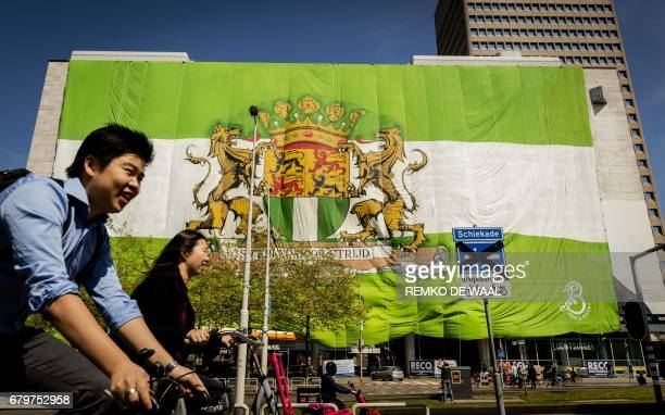 People cycle by a building covered with a flag placed by Feyenoord fans in the city center of Rotterdam May 6 2017 on the eve of the Dutch Eredivisie...