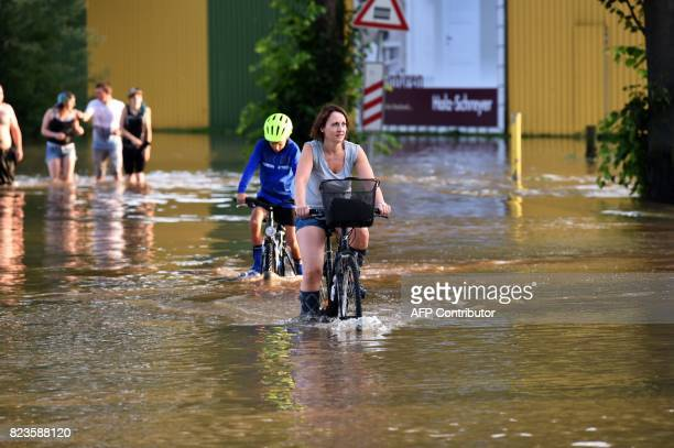 People cycle in a flooded street in Bad Salzdetfurth nothern Germany on July 27 2017 / AFP PHOTO / PATRIK STOLLARZ