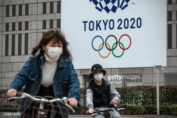 People cycle past a banner for the Tokyo Olympics on March 13, 2020 in Tokyo, Japan. Excluding the Diamond Princess cruise ship cases, the number of...