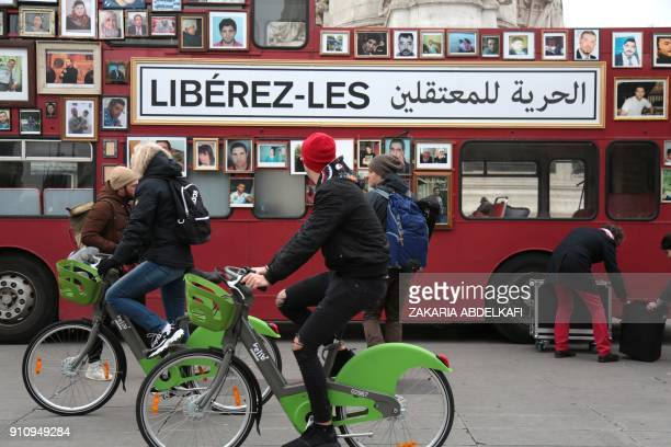 People cycle past a 'Freedom Bus' from the movement 'Families for Freedom' on the Place de la Republique in Paris on January 27 to demand freedom for...