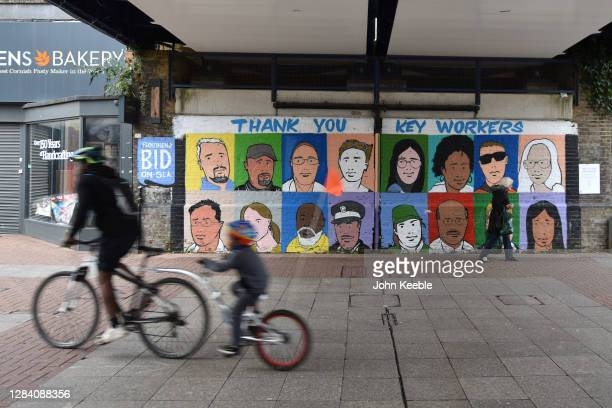 People cycle past a mural thanking key workers during the covid-19 pandemic in the High Street on October 28, 2020 in Southend-on-Sea, England.