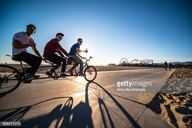 People cycling and jogging on Santa Monica beach, CA, USA