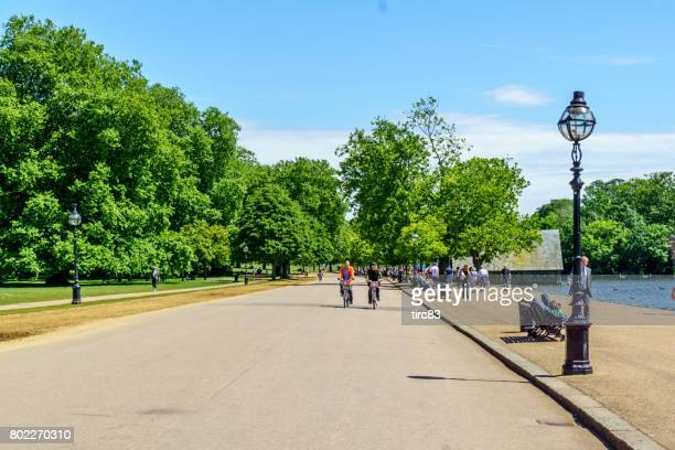 people cycling and walking in hyde park london - hyde park london stock photos and pictures