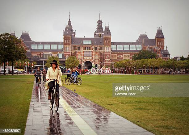 People cycling in early autumn during a rain shower through Museumplein with the infamous Rijksmuseum behind.