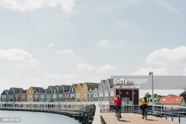 gens vélo près de bâtiments colorés, près du lac - rotterdam photos et images de collection
