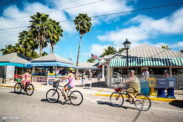 people cycling on key west streets - key west stock pictures, royalty-free photos & images