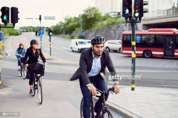people cycling on street in city - sportschutzhelm stock-fotos und bilder