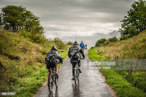 People Cycling On Wet Road Amidst Trees Against Cloudy Sky