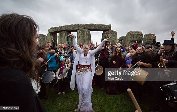 People dance and listen to drums being played outside the stones as druids pagans and revellers gather at Stonehenge hoping to see the sun rise as...
