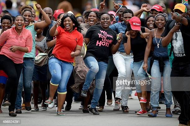 People dance and they gather in Mthatha waiting for the funeral cortege of former South African president Nelson Mandela to pass by on its way to his...