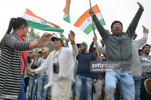 People dance and wave the national flag as they wait for the return of Indian pilot Indian Air Force Wing Commander Abhinandan Varthaman at the...