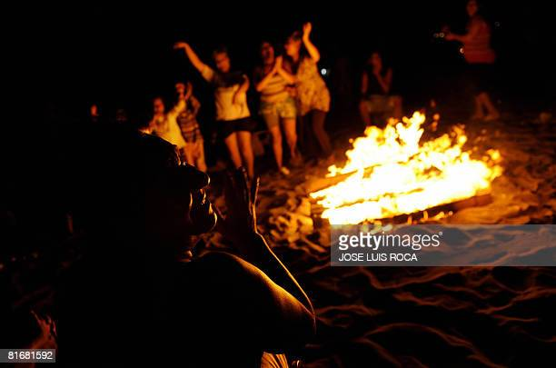People dance around a bonfire early on June 24 during the traditional San Juan night on a beach in the southern Spanish city of Malaga Fires are lit...