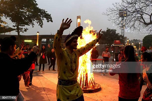 People dance around bonfire during the Lohri celebrations on January 13, 2016 in Noida, India. Lohri celebrates the harvest of rabi crops, those...