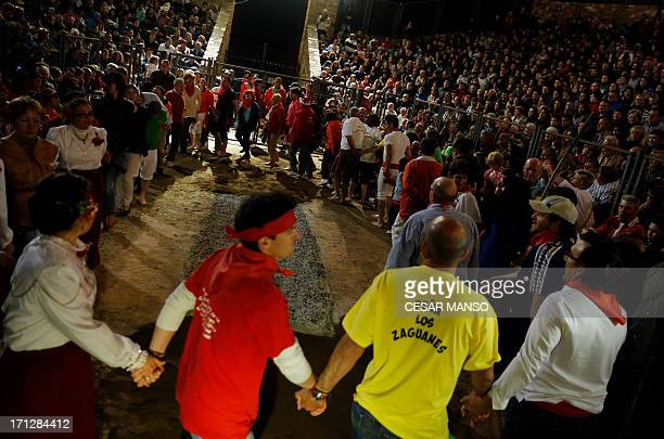 People dance around of burning embers during the night of San Juan in San Pedro Manrique, Soria province in northern Spain early on June 24, 2013....