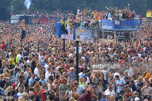 People dance around trucks blaring techno music during the annual Love Parade July 12 2003 in Berlin Germany Hundreds of thousands of Techno fans...