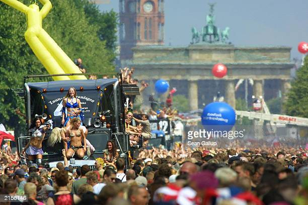 People dance around trucks blaring techno music near the Brandenburg Gate during the annual Love Parade July 12 2003 in Berlin Germany Hundreds of...