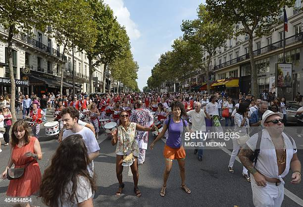 People dance as a Batucada drum band performs on September 7 2014 in a street of Paris as part of a 'Peace parade' organized by the Brazilian...
