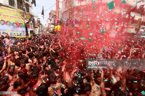 People dance as they throw coloured powder and spray water during Holi celebrations, amid the COVID-19 pandemic, in Prayagraj, India's northern state...