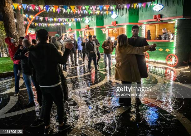 People dance at a Nowruz holiday market in Baku on March 20 2019 Nowruz marks the first day of spring and the beginning of the year in the Persian...