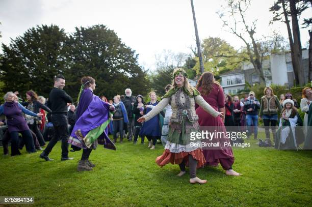 People dance at Chalice Well Glastonbury where Beltane festivities are taking place on May Day