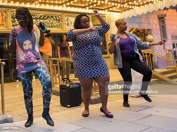 TOPSHOT People dance during a candle light vigil in remembrance to Prince outside the Warner Theatre in Washington DC on April 21 2016 Emergency...