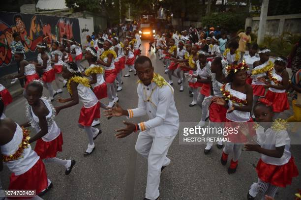 People dance during a Christmas Parade on the streets of the commune of Petion Ville in the Haitian capital PortauPrince on December 23 2018