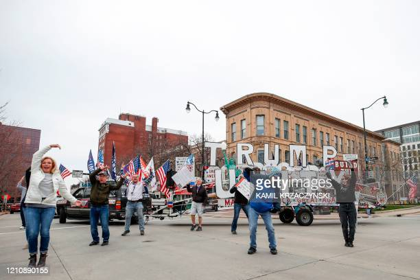 People dance during a protest against the coronavirus shutdown in front of State Capitol in Madison Wisconsin on April 24 2020 Gyms hair salons and...