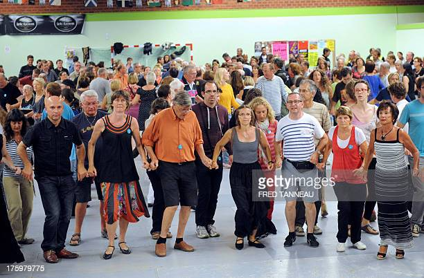 People dance during the Fest Noz a Breton traditional festival with dancing in groups and live musicians playing acoustic instruments part of the...