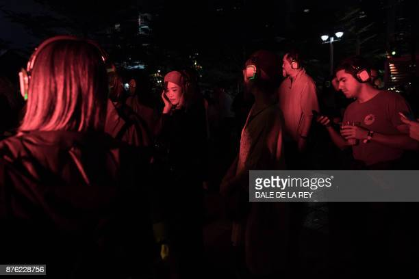 People dance during the 'silent disco' at the Clockenflap music festival in Hong Kong on November 19 2017 / AFP PHOTO / DALE DE LA REY