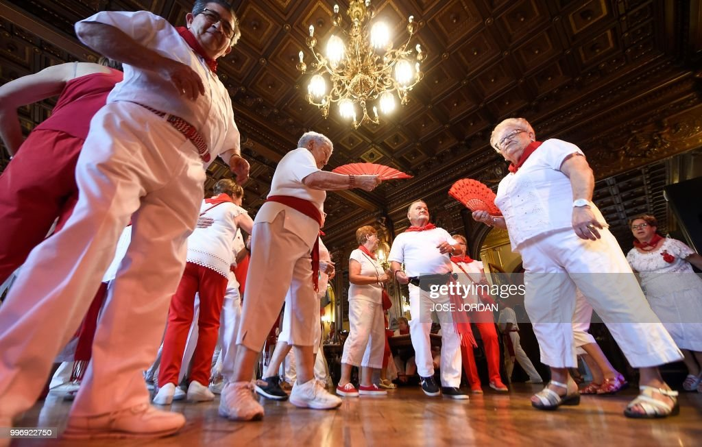 People dance during the traditional 'Baile de la Alpargata' (the Espadrille dance) during the San Fermin Festival in Pamplona, northern Spain, on July 12, 2018. - Each day at 8am hundreds of people race with six bulls, charging along a winding, 848.6-metre (more than half a mile) course through narrow streets to the city's bull ring, where the animals are killed in a bullfight or corrida, during this festival dating back to medieval times and also featuring religious processions, folk dancing, concerts and round-the-clock drinking.