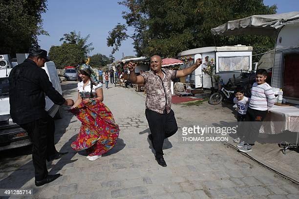 People dance in a Roma camp set up in SaintDenis northern Paris suburbon October 4 2015 AFP PHOTO / THOMAS SAMSON
