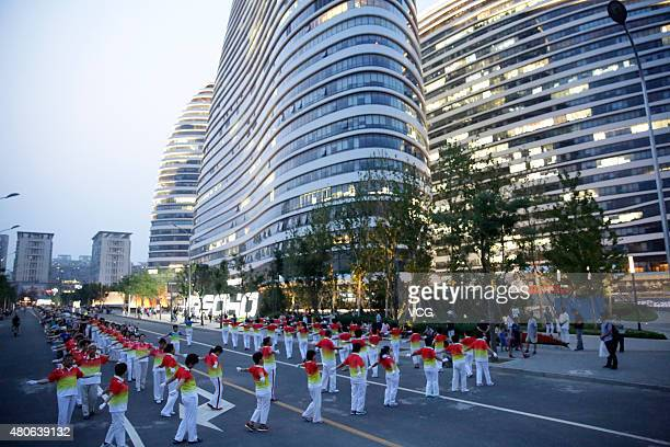People dance in front of the Wangjing Soho at night on July 8 2015 in Beijing China The dance team has uniforms and more than 200 members
