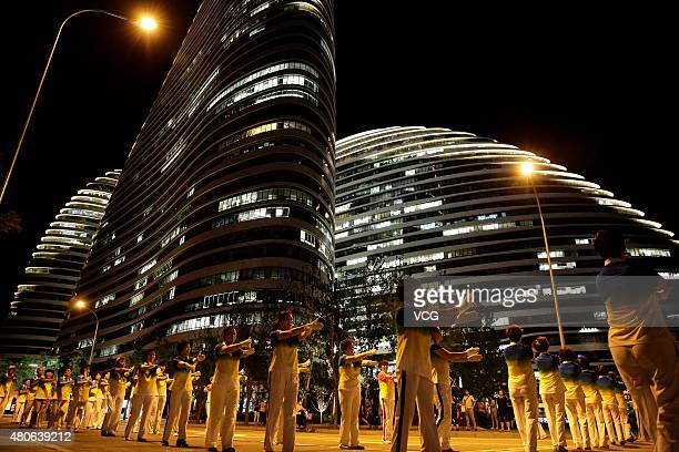 People dance in front of the Wangjing Soho at night on June 30 2015 in Beijing China The dance team has uniforms and more than 200 members