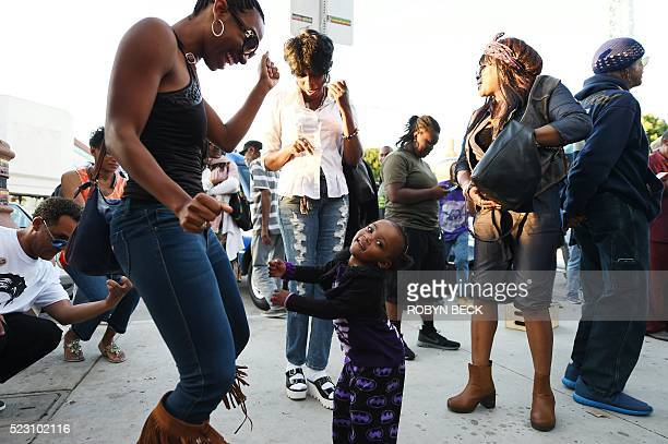 People dance in the street to the of Prince at Leimert Park in Los Angeles California where fans gathered to celebrate and remember the pop music...