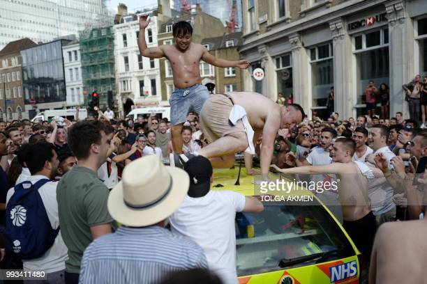 People dance on a NHS ambulance as fans celebrate in the street beside Borough Market after England's win over Sweden in the Russia 2018 World Cup...