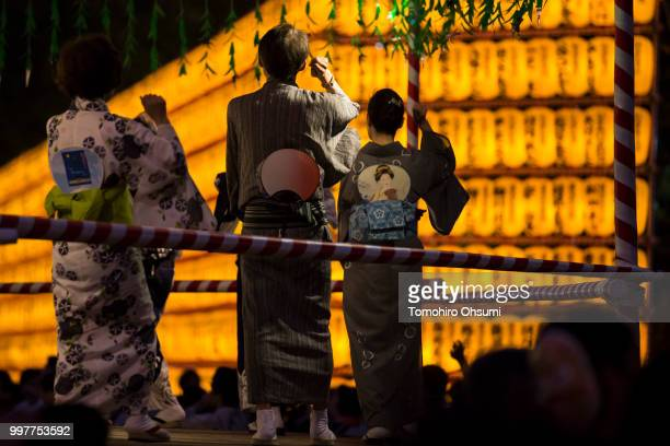 People dance on a stage in front of lit paper lanterns during the Mitama Matsuri summer festival at the Yasukuni Shrine on July 13 2018 in Tokyo...