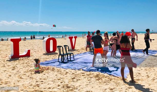 People dance on the beach in Playacar on Saint Valentine's Day near the seaside tourist resort of Playa del Carmen Quintana Roo State on February 14...
