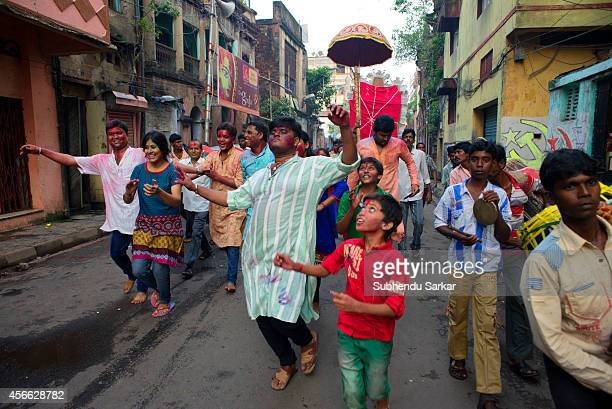 People dance on the road while taking the idol of goddess Durga is carried to the Hooghly river for immersion on the last day of Durga puja festival...