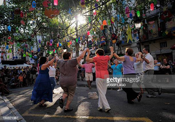 People dance the typical Catalan dance 'La Sardana' in a street during a local festival in Barcelona's Gracia neighborhood on August 15 2012 One of...