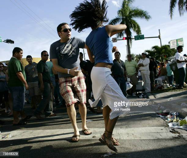 People dance to the tune of the salsa music playing as they attend the annual Calle Ocho celebration March 11 2007 in Miami Florida The event is...