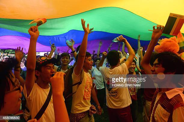 People dance under a large rainbow flag during Vietnam's gay pride parade in Hanoi on August 3 2014 Some 300 people joined a colourful bike parade...