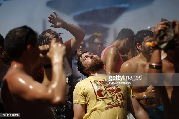 People dance under spraying water at Do LaB at the Coachella Valley Music Arts Festival at the Empire Polo Club in Indio California April 12 2014 The...