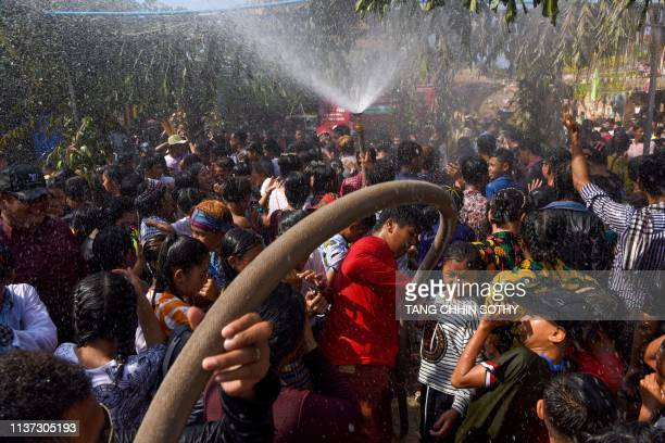 People dance under spraying water during Khmer New Year celebrations at a pagoda in Phnom Penh on April 15 2019