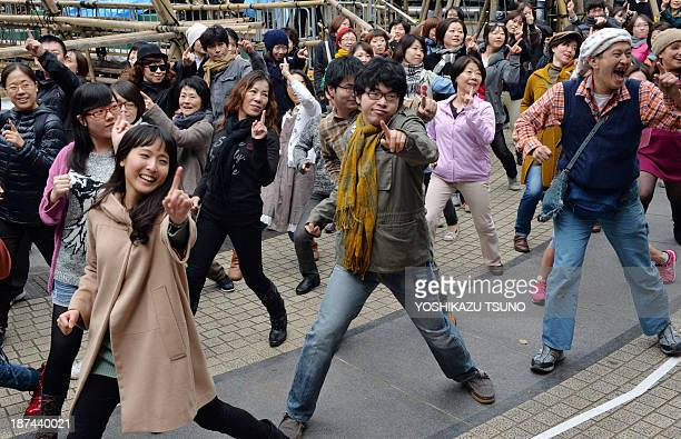 People dance Yellow Magic Orchestra's 'Rydeen' in a flashmob event coreographed by Ryohei Kondo in Tokyo on November 9 2013 as a part of art...