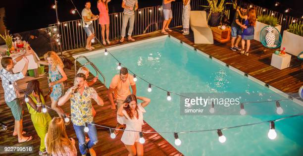 people dancing and having good time at night party by pool - pool party stock pictures, royalty-free photos & images