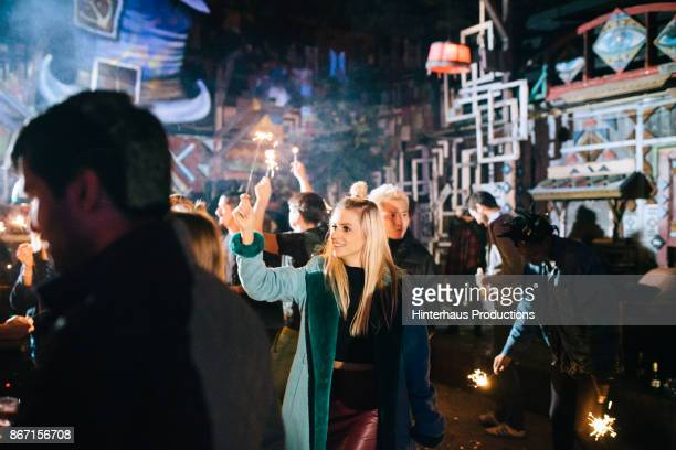 People Dancing And Waving Sparklers At Colourful Nightclub