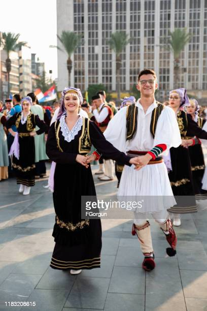 people dancing in balkan traditional clothing at the festival - folk music stock pictures, royalty-free photos & images